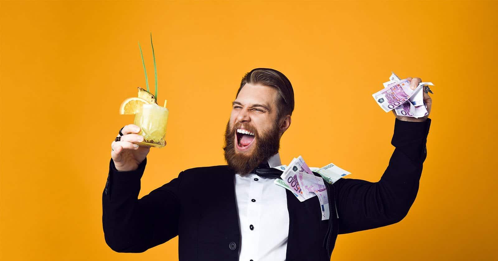 freudiger Mann mit Geld und Cocktail in der Hand
