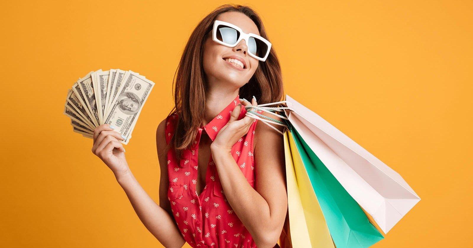 Frau mir Sonnenbrille trägt Shoppingtüten und einen Fächer aus Geld