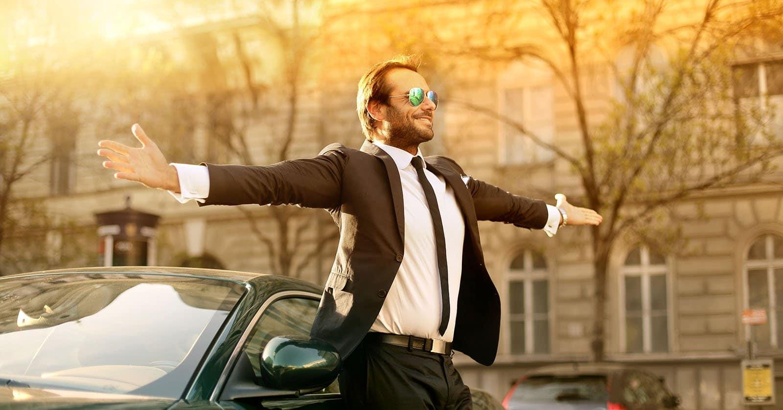 Mann in Anzug und Sonnenbrille steht mit ausgestreckten Armen vor einem Auto