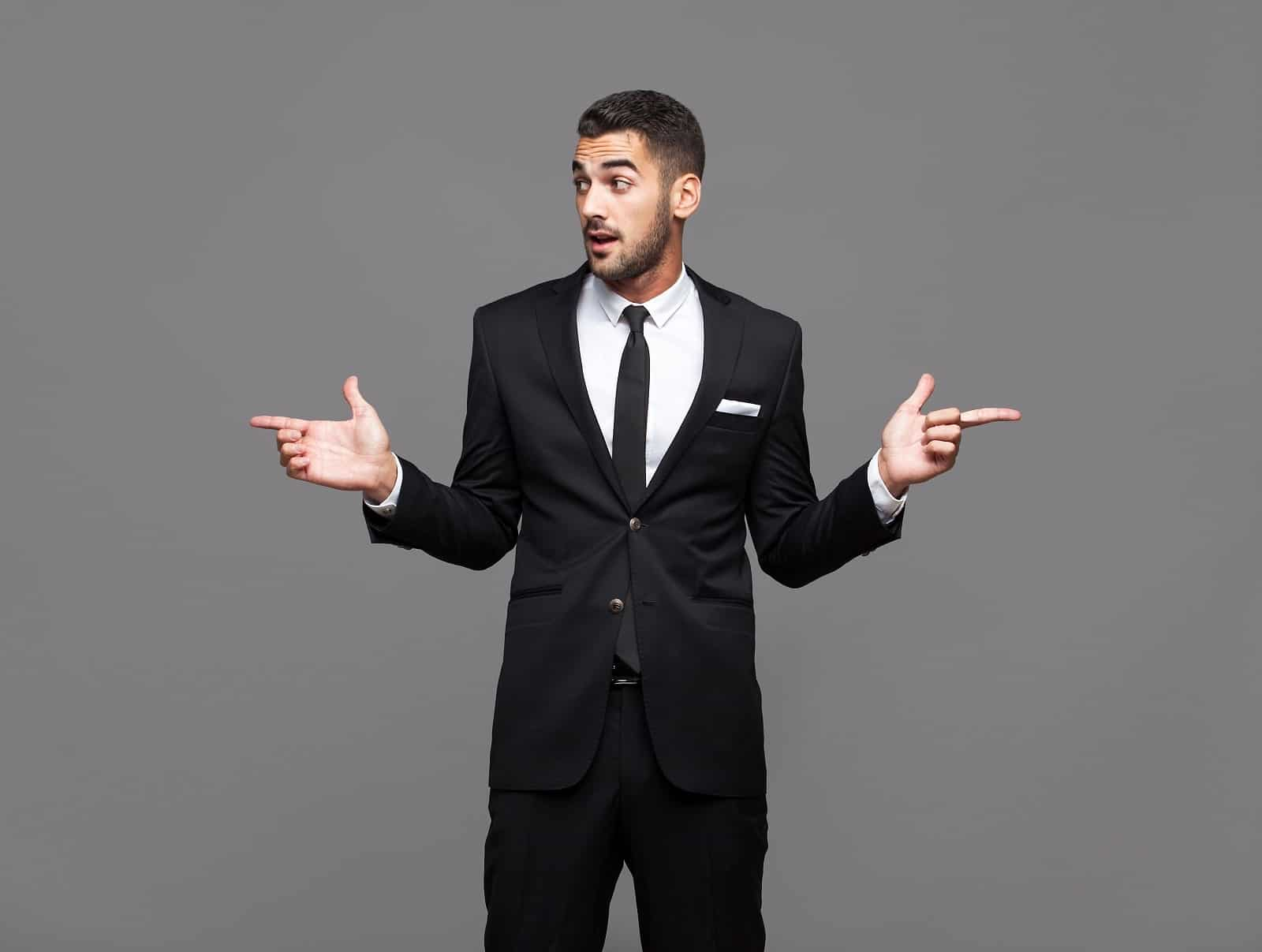 Mann mit Anzug steht in einem Raum mit ausgestreckten Fingern nach rechts und links
